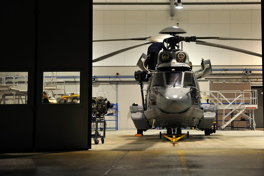 An Airbus H225M military helicopter is parked inside a hangar for maintenance.