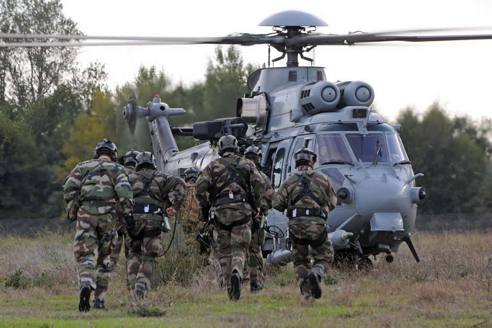 A group of military personnel advance toward an on-ground Airbus H225M helicopter.