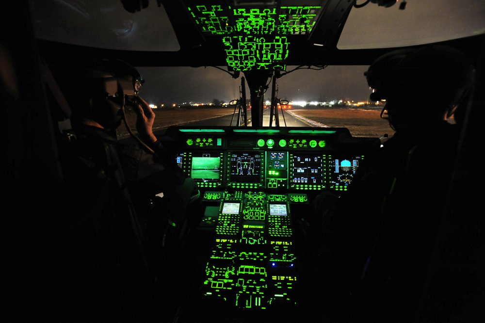 The NH90 helicopter's flight controls and panels are illuminated inside the cockpit.