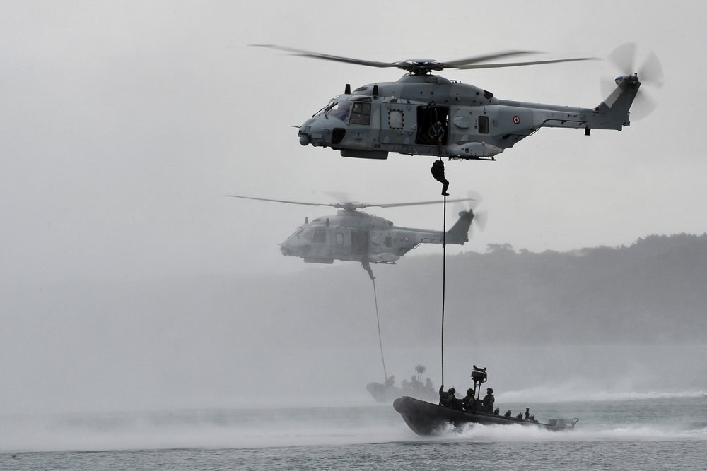 Two NH90 NFH helicopters hover in formation while military personnel rappel down to sea vessels.