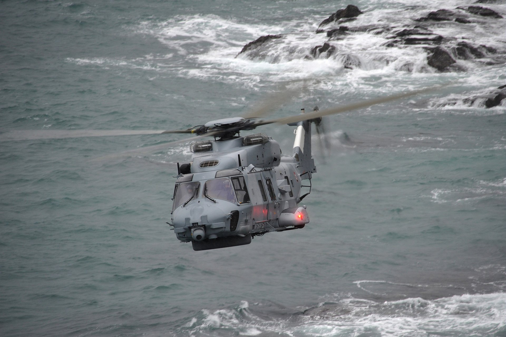 Head-on view of an NH90 NFH military helicopter flying over a coastal area.
