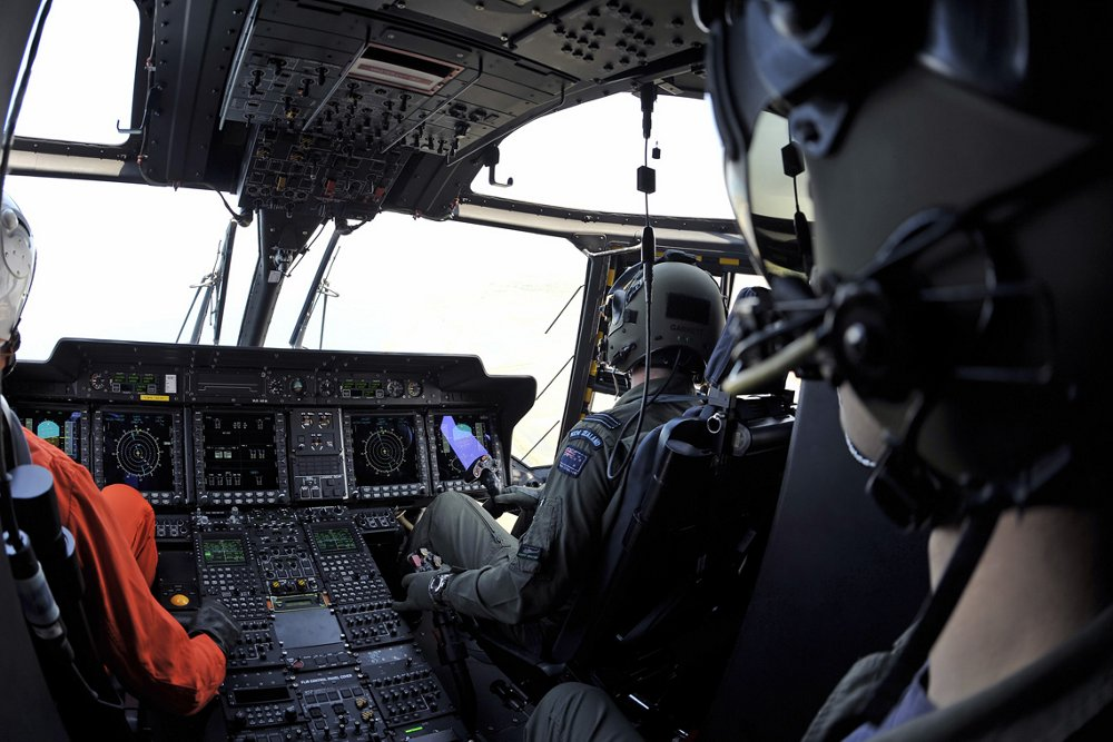 Photo of the flight crew and controls inside an NH90 helicopter's cockpit.