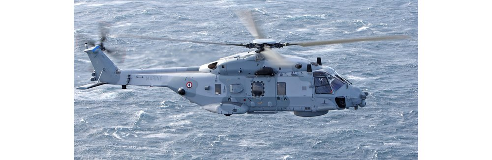 Side view of an NH90 NFH military helicopter flying over water.