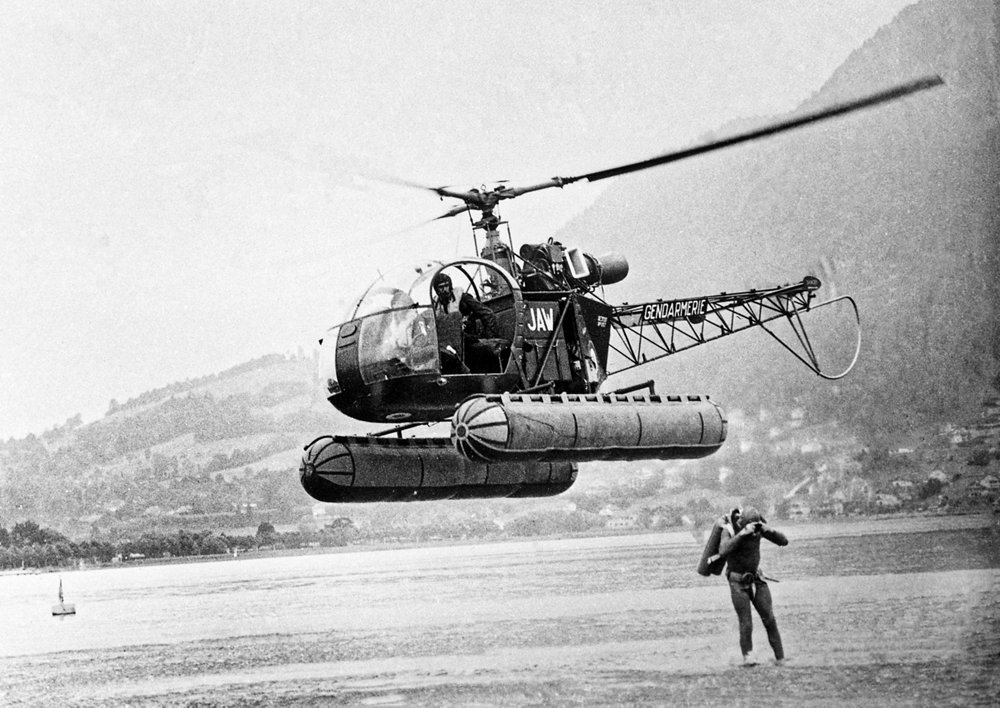 "An SE3130 ""Alouette II"" helicopter is shown during training exercises over Lake Annecy in France."