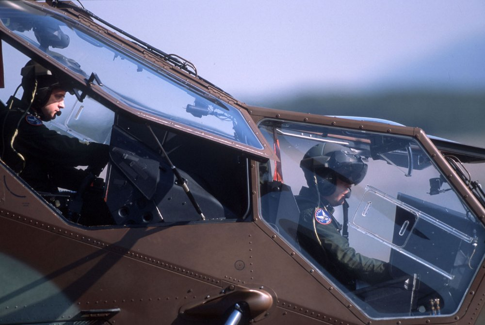 A side view of an Airbus Tiger HAD multi-role attack helicopter's tandem-seat glass cockpit with two pilots inside.