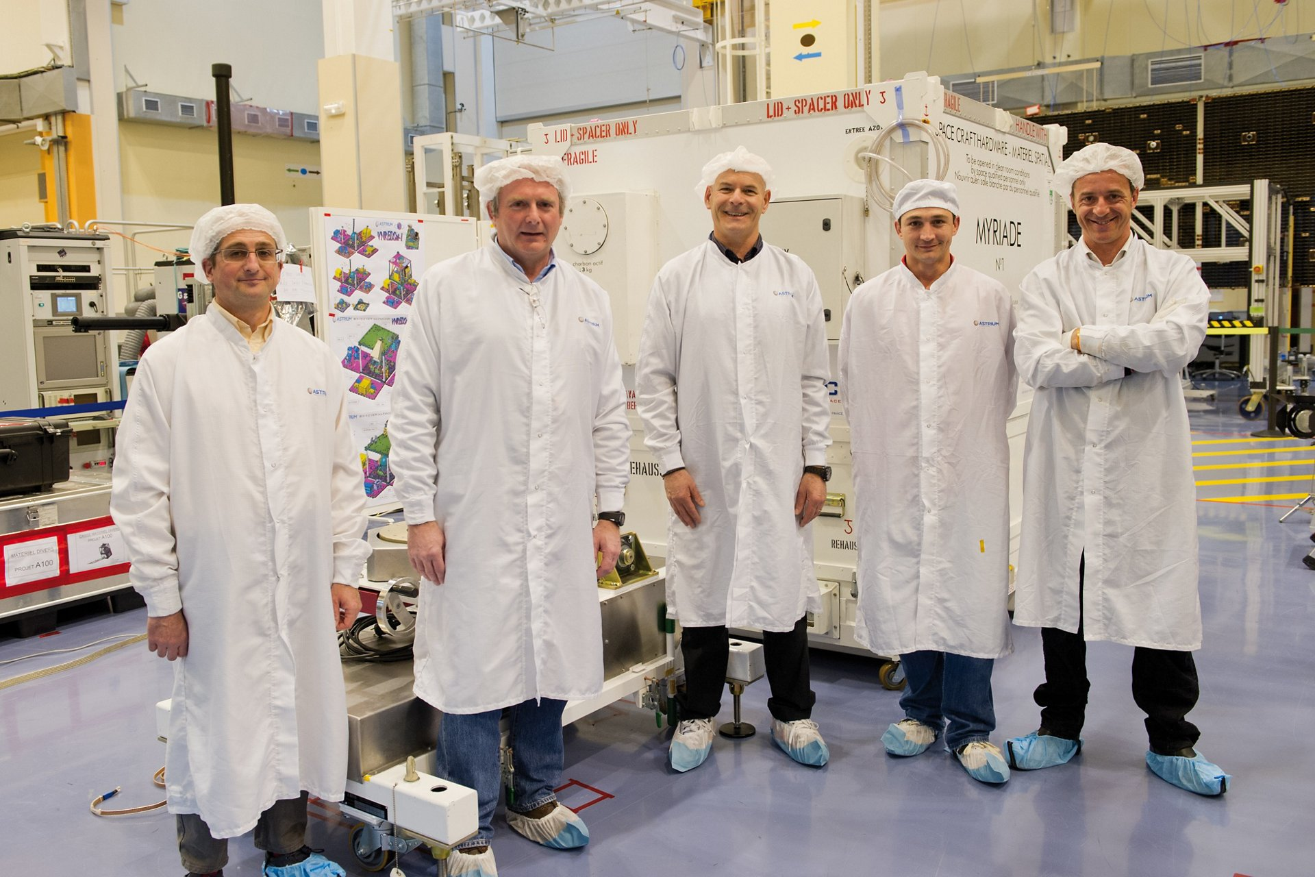 A group of Airbus satellite engineers inside a clean room facility.