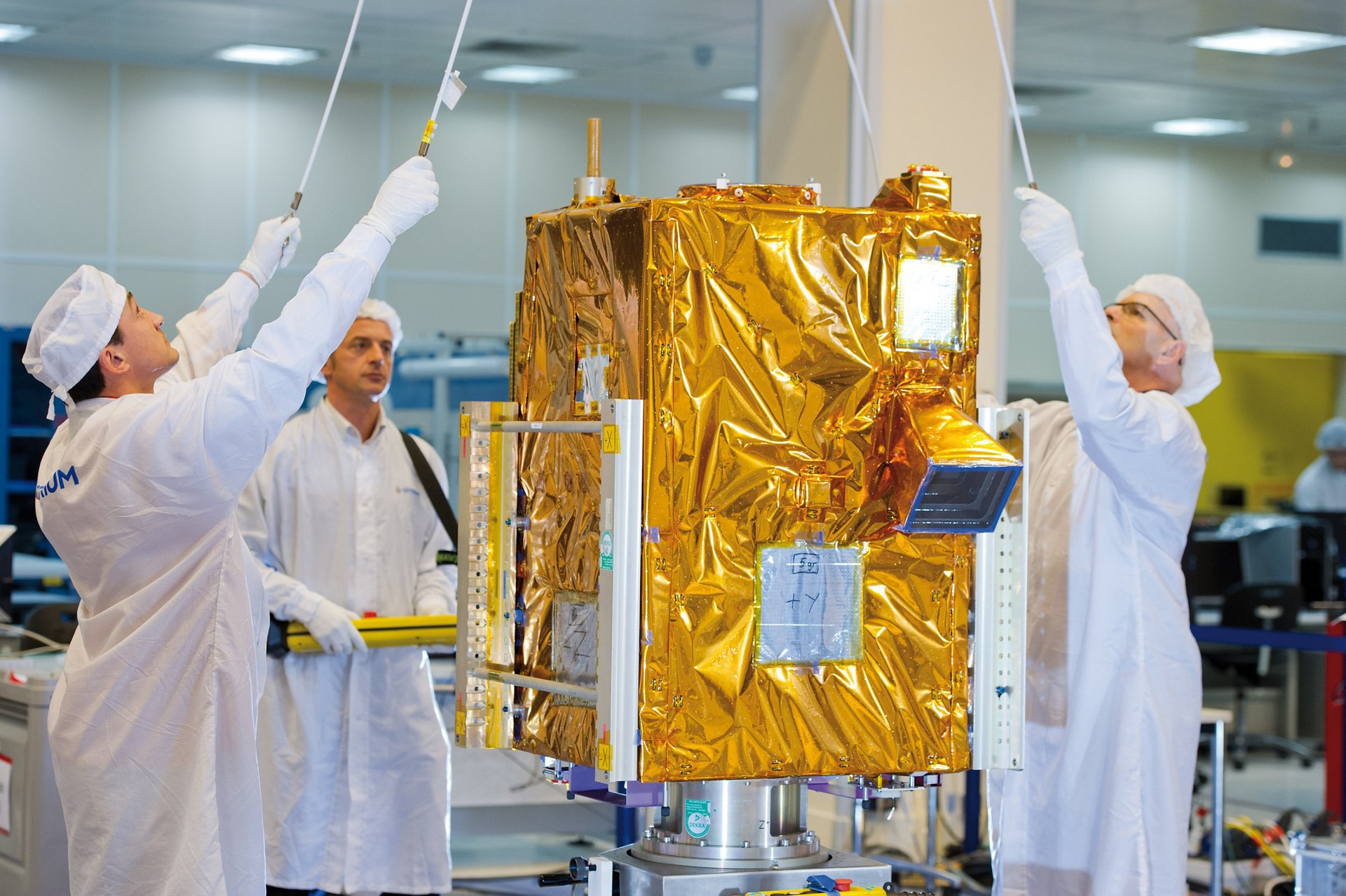 Airbus engineers ready the VNREDSat-1 Earth observation satellite in a clean room setting.