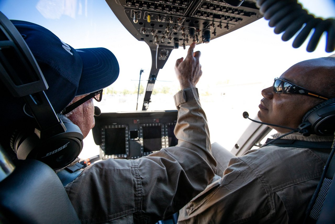 Pilots check systems inside a helicopter