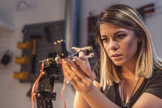 Young woman fixing a robot arm in a workshop.