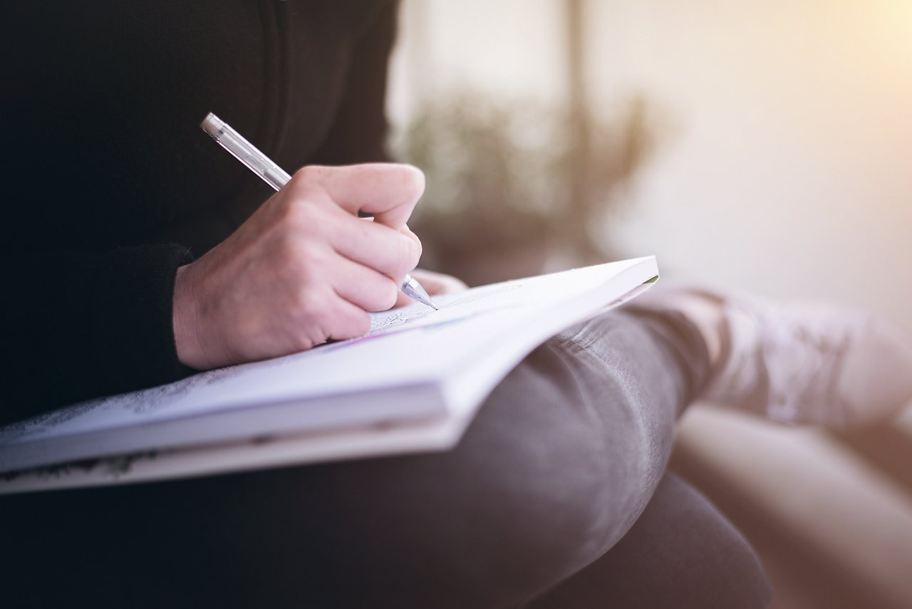 woman writing or scribbling on a notepad that is resting on her legs