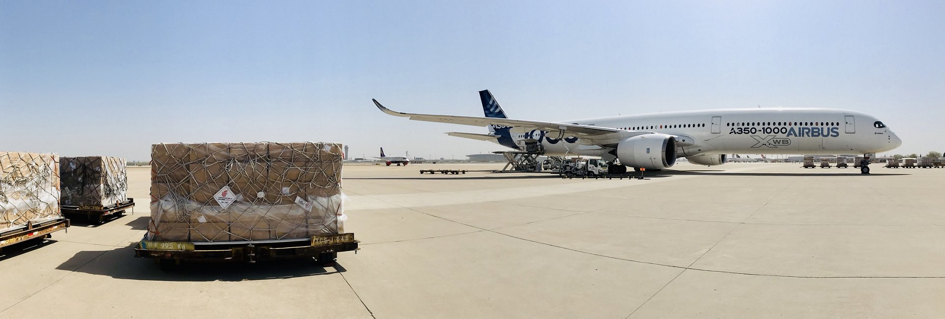 This wide-angle photo shows the A350-1000 in Tianjin, China with a shipment of protective face masks in the foreground, ready for loading and delivery to Europe
