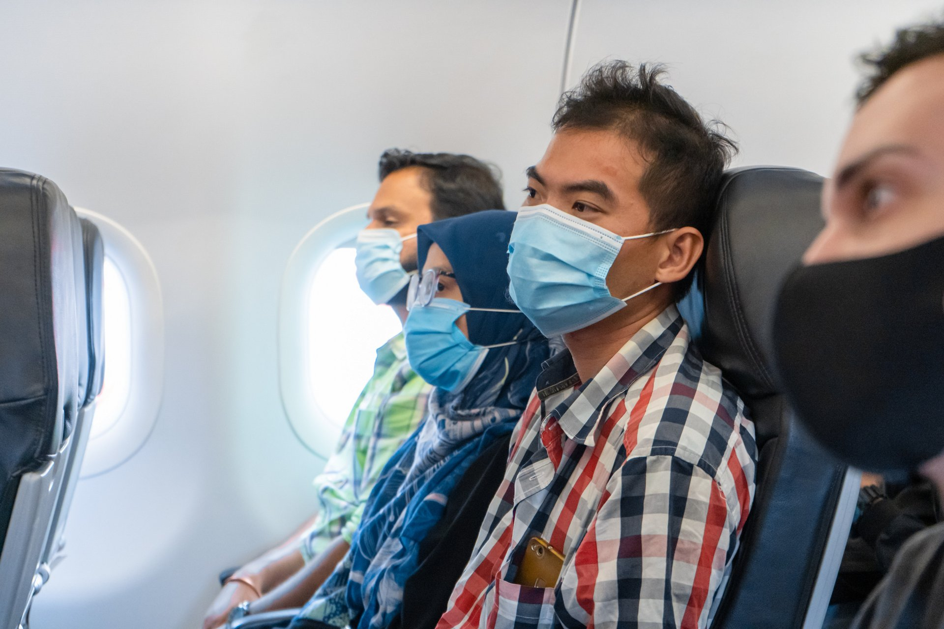 Airplane passengers are wearing medical masks on their faces. Air travel during the coronavirus pandemic.