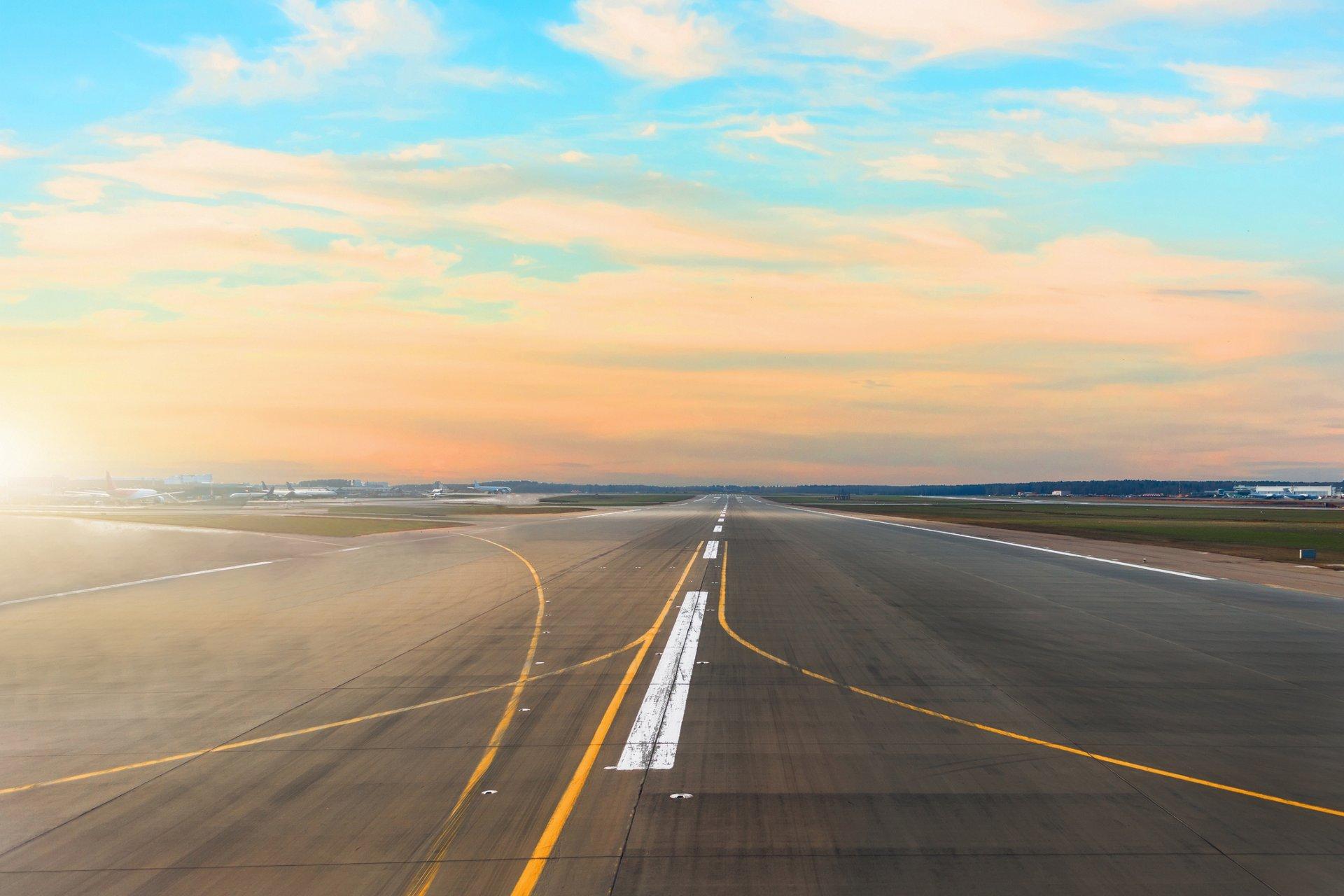机场跑道后日落地平线和如画的卷云在天空中