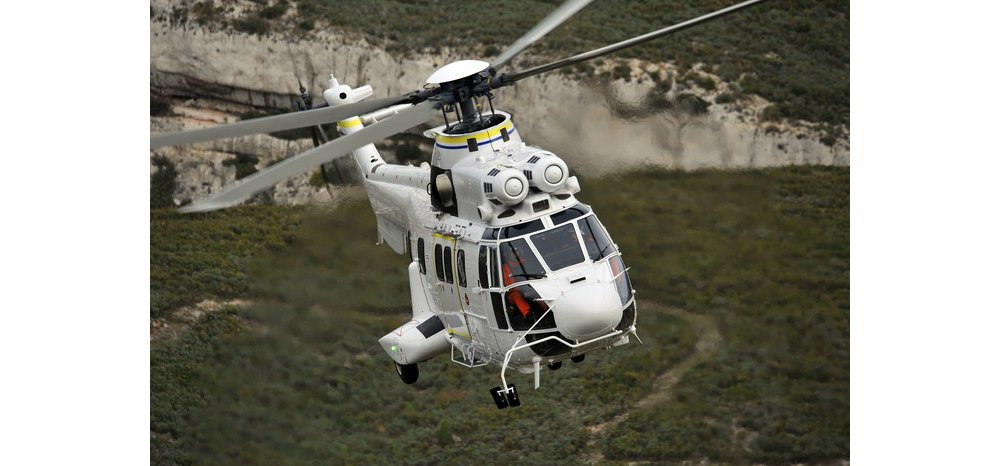 An Airbus H225 helicopter flies over varied terrain.