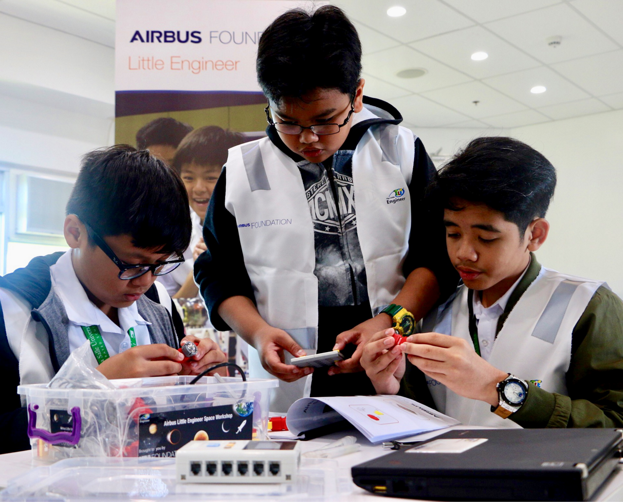 Three students collaborate during an Airbus Little Engineer workshop event in Singapore.