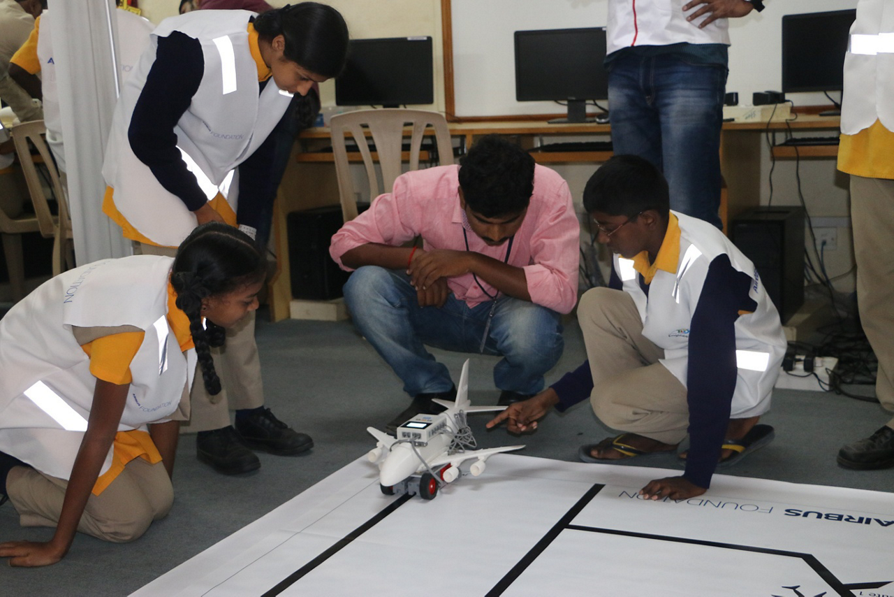 Students gather around their aviation-focussed science project during an Airbus Little Engineer event in Bengaluru, Indira.