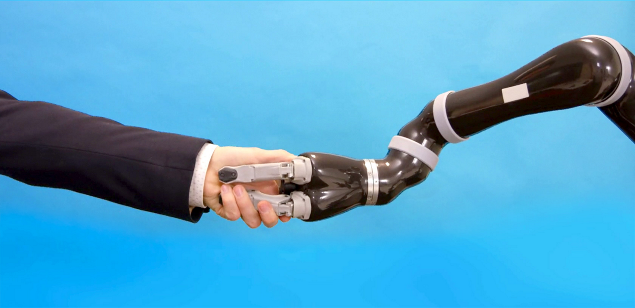 A human arm shakes hands with a robot arm.