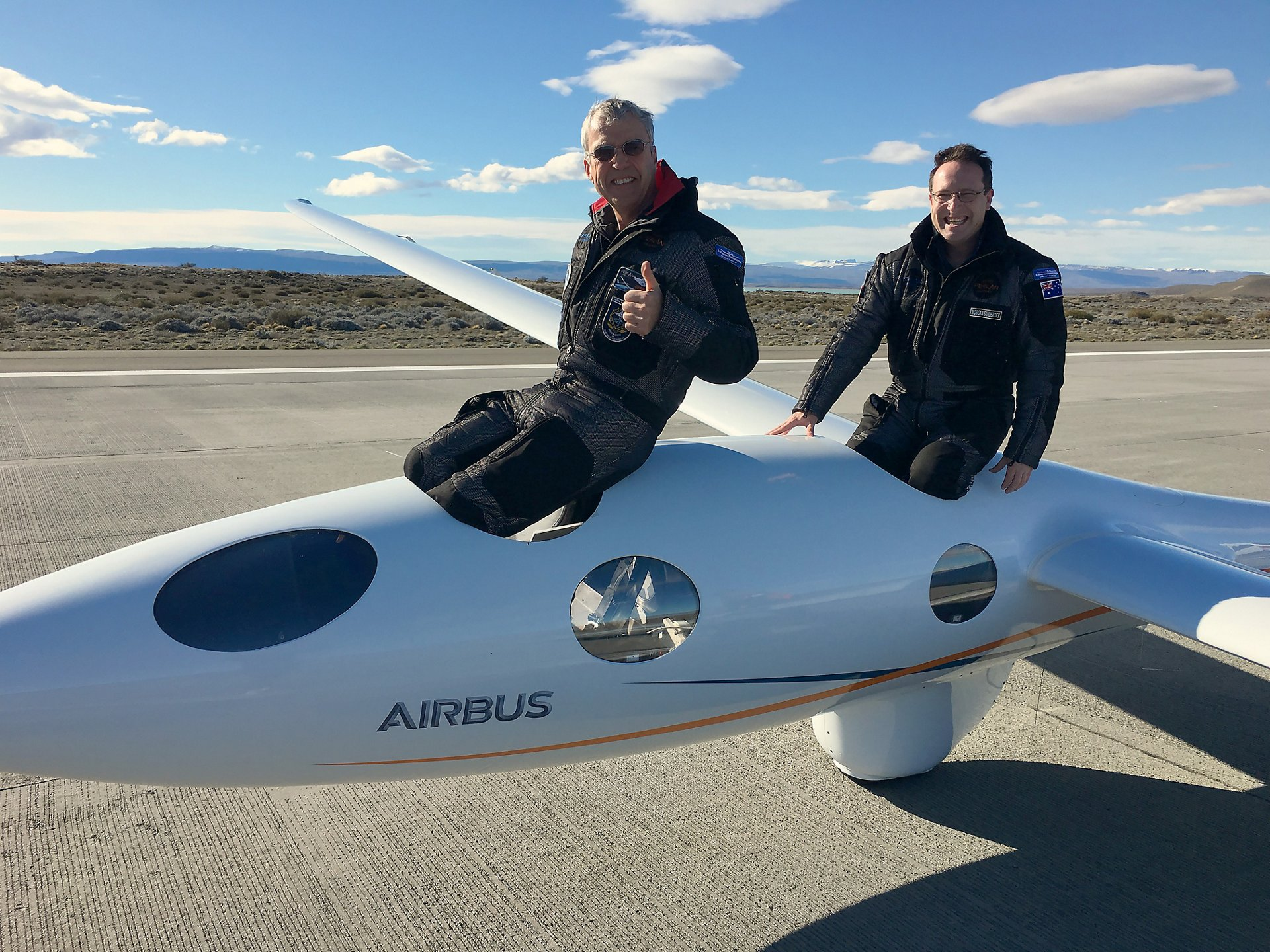 "Airbus Perlan Mission II pilots Jim Payne (left) and Morgan Sandercock emerge from the cockpit after setting a new glider world altitude record Sept. 3, soaring to 52,172 feet in the pressurized craft that was carried aloft by rare ""stratospheric mountain waves"" in the Andes Mountains near El Calafate, Argentina. Photo by Jackie Payne, Perlan Project."