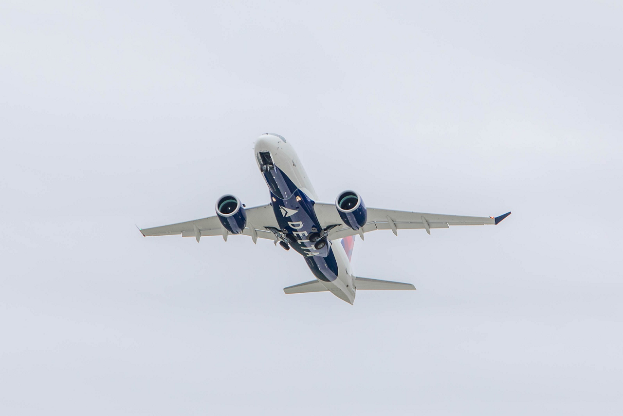 An Airbus A220-100 in Delta Air Lines' livery ascends after takeoff.