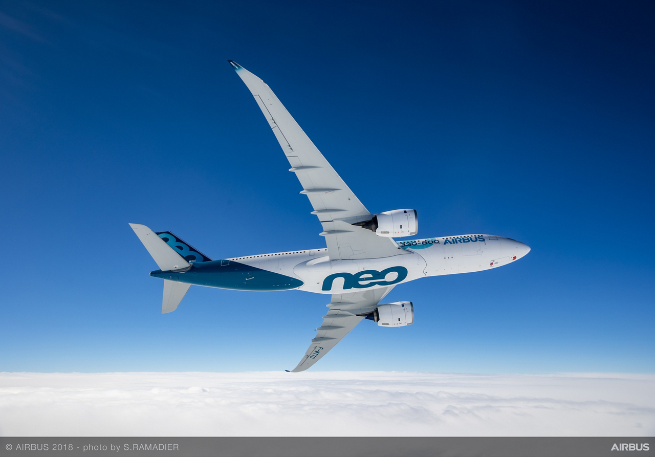 An in-flight photo of a banking Airbus A330neo commercial aircraft.