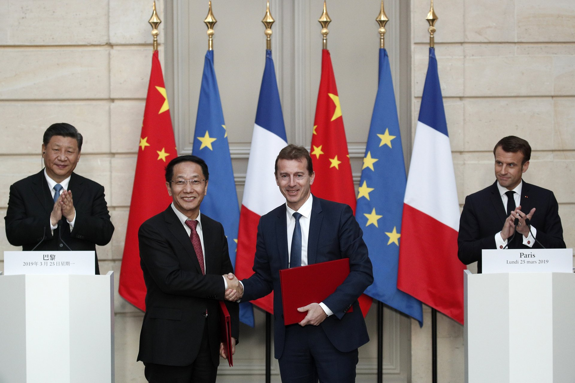 French President Emmanuel Macron (R) and Chinese President Xi Jinping (L) applaud as President of Airbus's commercial aircraft business, Guillaume Faury (2nd R) and Chairman of China Aviation Supplies Co (CASC) Jia Baojun (2nd L) shake hands during an agreement signing ceremony  at the Elysee Palace in Paris on March 25, 2019, as part of a state visit. - The Chinese president is on a  three-day state visit to France where he is expected to sign a series of bilateral and economic deals on energy, the food industry, transport and other sectors. (Photo by Yoan VALAT / POOL / AFP)