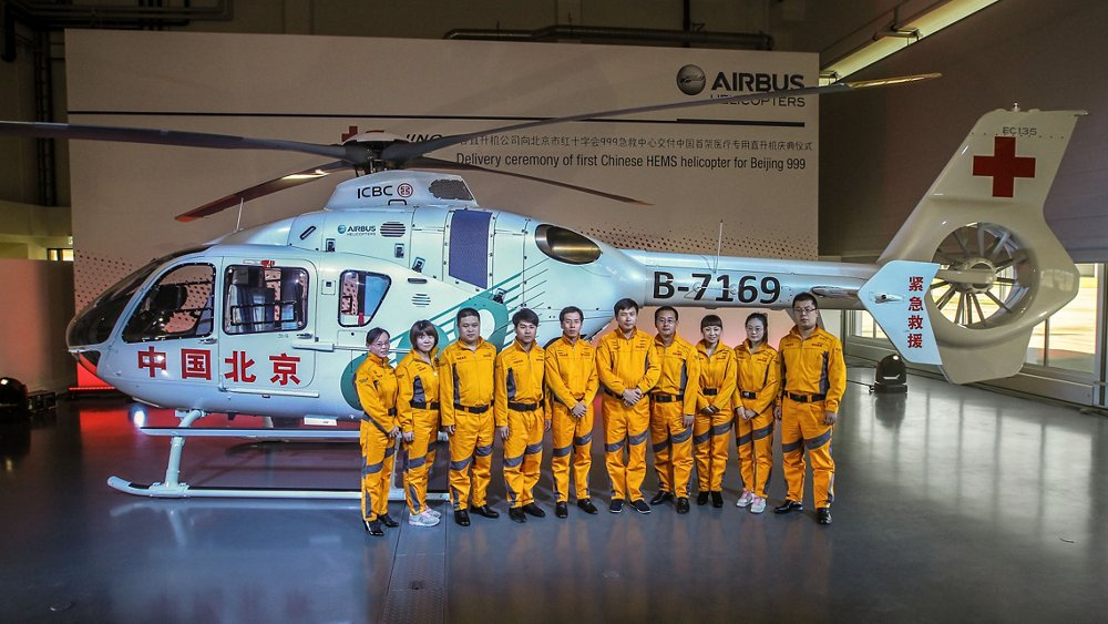 Chinese emergency medical service workers stand in front of an Airbus H135 helicopter.