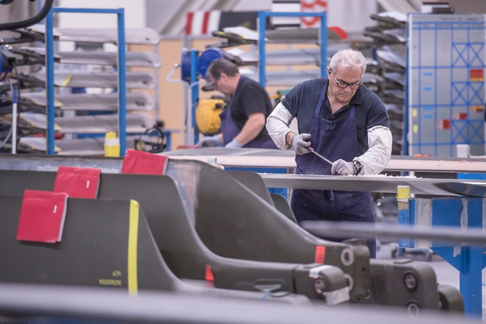 An employee repairs a helicopter blade at Airbus' new Paris-Le Bourget blade production site
