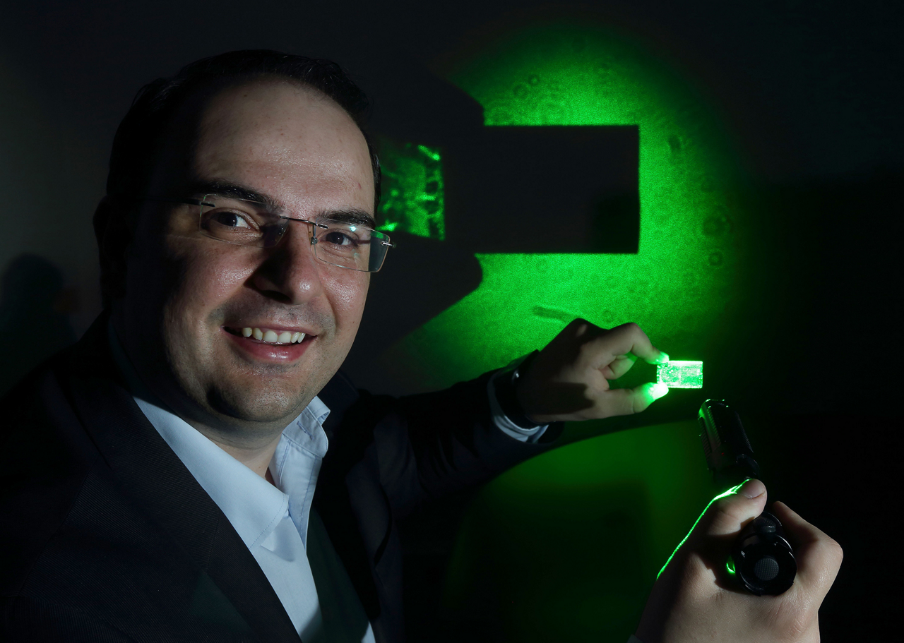 Lamda Guard President and CEO George Palikaras demonstrates the capability of his company's thin transparent films, which are specifically designed to block potentially harmful laser sources