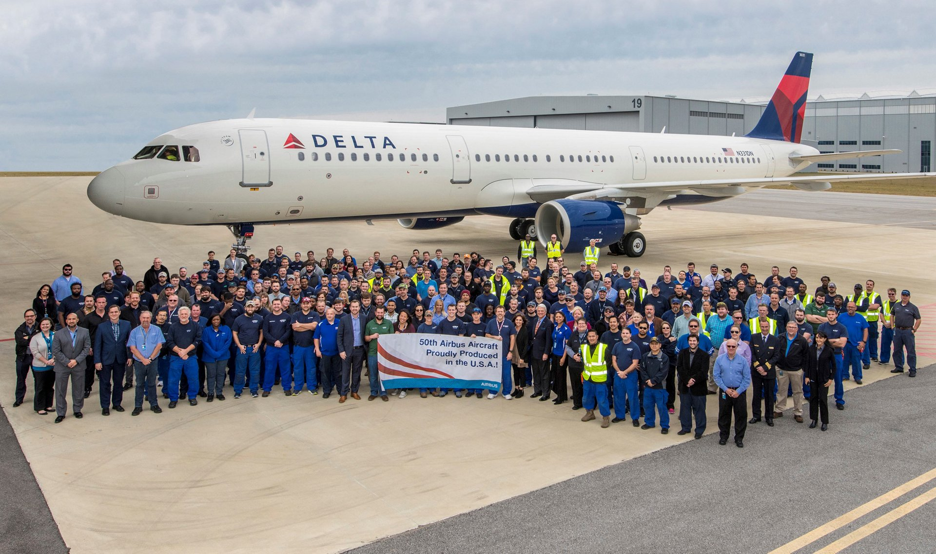 Team members at the Airbus U.S. Manufacturing Facility gather in front of the 50th jetliner delivered from Mobile, Alabama – an A321 for Delta Air Lines, in a milestone that also meets the industrial site's goal of reaching the production rate of four A320 Family jetliners per month