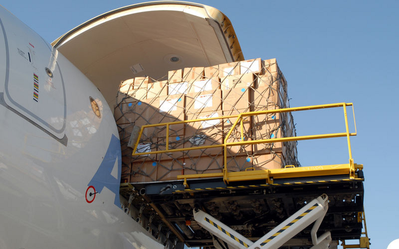 A shipment is loaded onto an Airbus A330-200F through the freighter's main deck cargo door