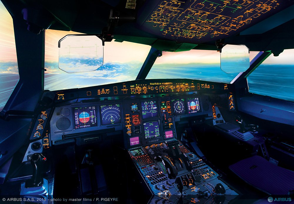 A full view of the flight controls inside an Airbus A330neo cockpit, including head-up display for the pilots