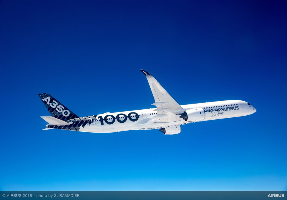 Side view of an Airbus A350-1000 in Airbus livery, flying in clear blue skies.