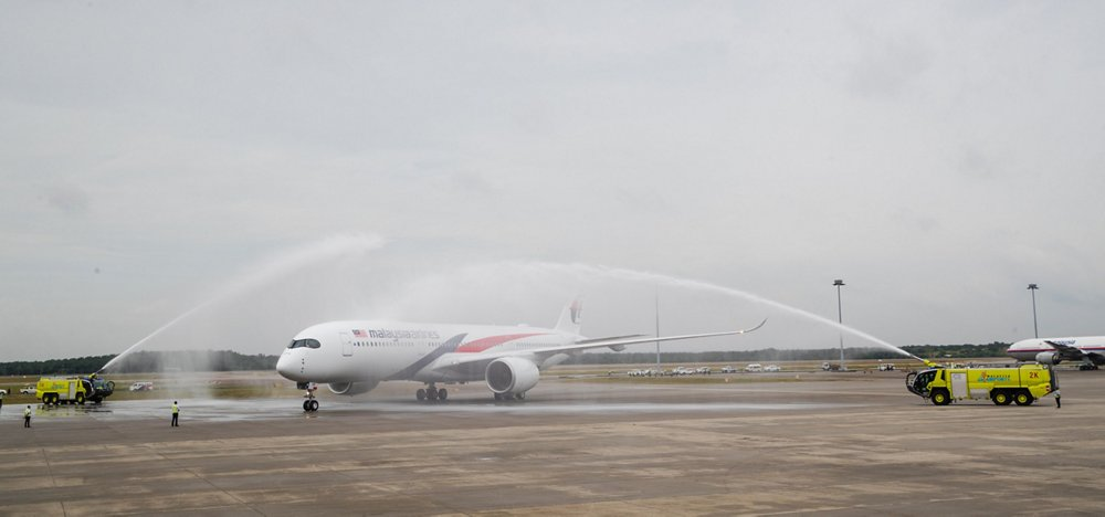 Malaysia Airlines' first A350-900 passes under a water cannon salute at Kuala Lumpur International Airport after arriving on its delivery flight