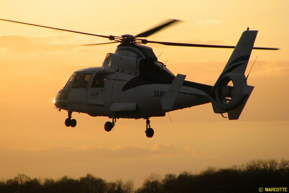 A rear view of a Mont Blanc Helicopters-operated AS365 flying during sunset.