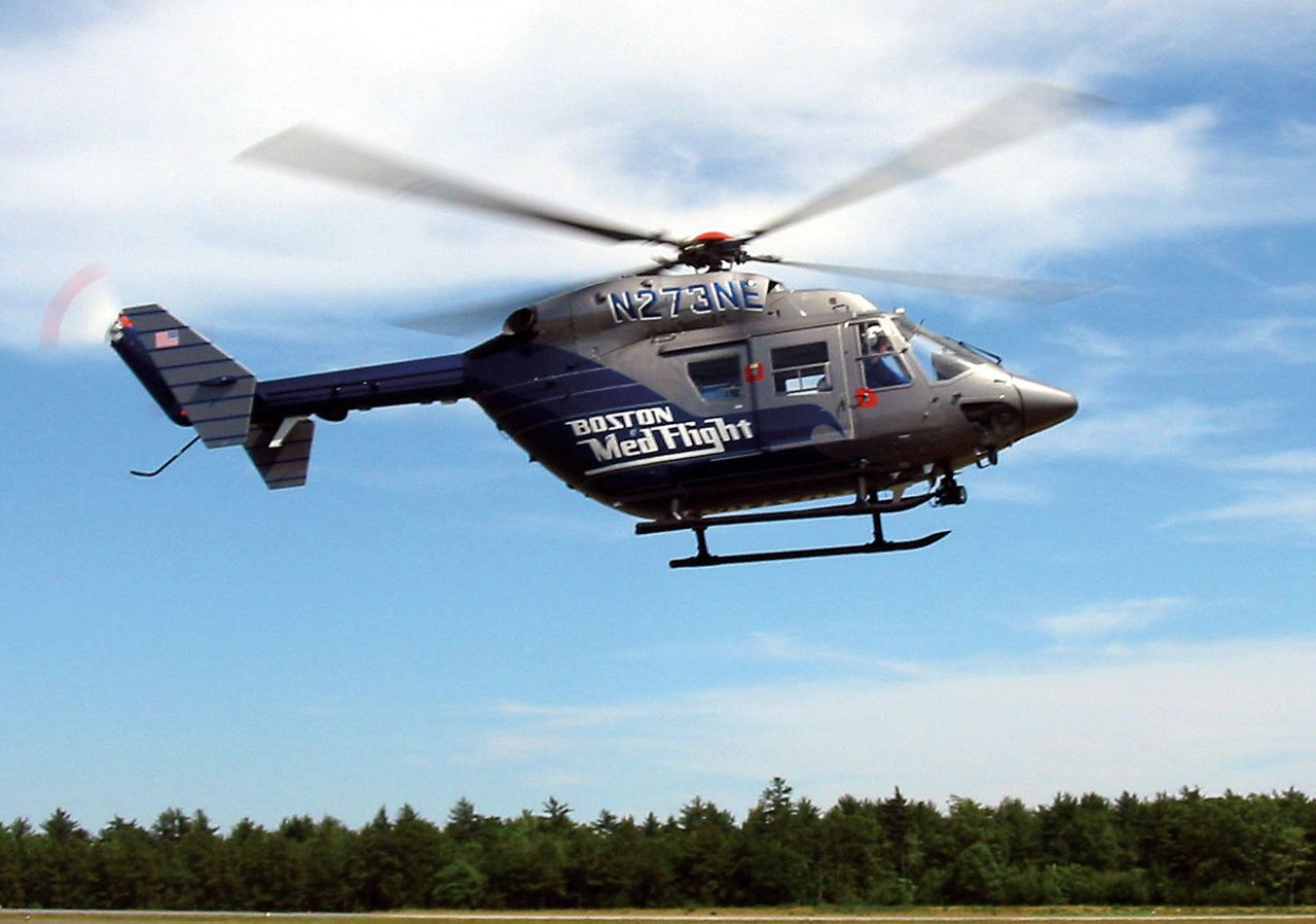 A view of an in-flight BK117 in the livery of Helicopter Emergency Medical Services (HEMS) provider Boston MedFlight.