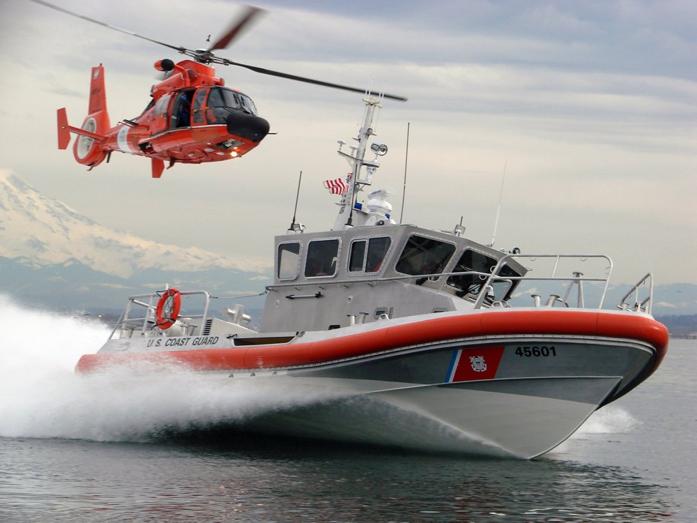 An in-flight Airbus AS565 MBe helicopter delivered to the U.S. Coast Guard trails a speeding Coast Guard vessel.
