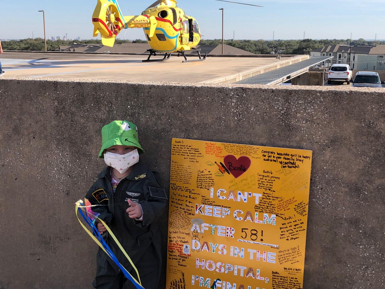 Bodhi takes a commemorative photo with Methodist AirCare's EC135 helicopter visible in the background.