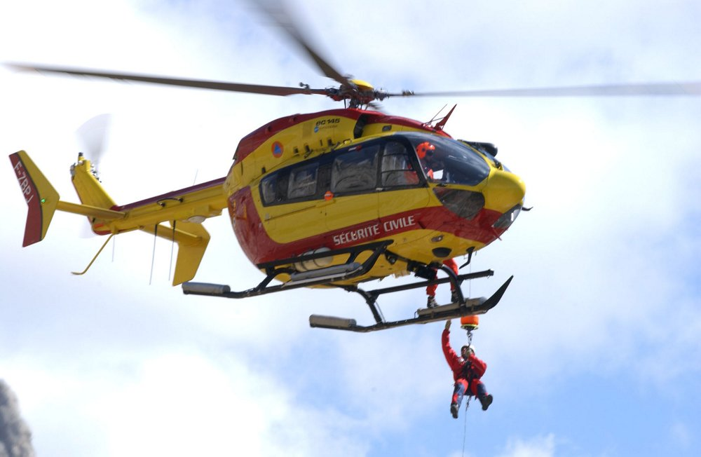 Team members are lowered to the ground by an in-flight EC145 helicopter delivered to the French Sécurité Civile agency.