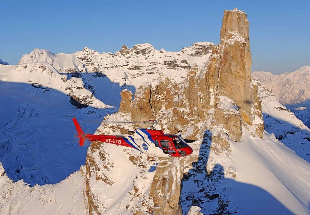An Airbus H125 helicopter is operated above snow-covered, mountainous terrain