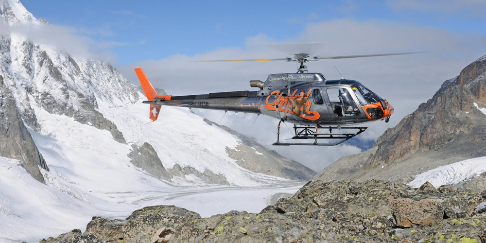 An Airbus H125 helicopter hovers above mountainous terrain