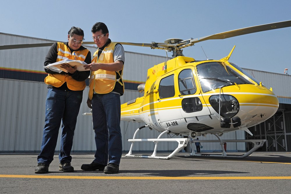 Two engineers review helicopter maintenance documentation.