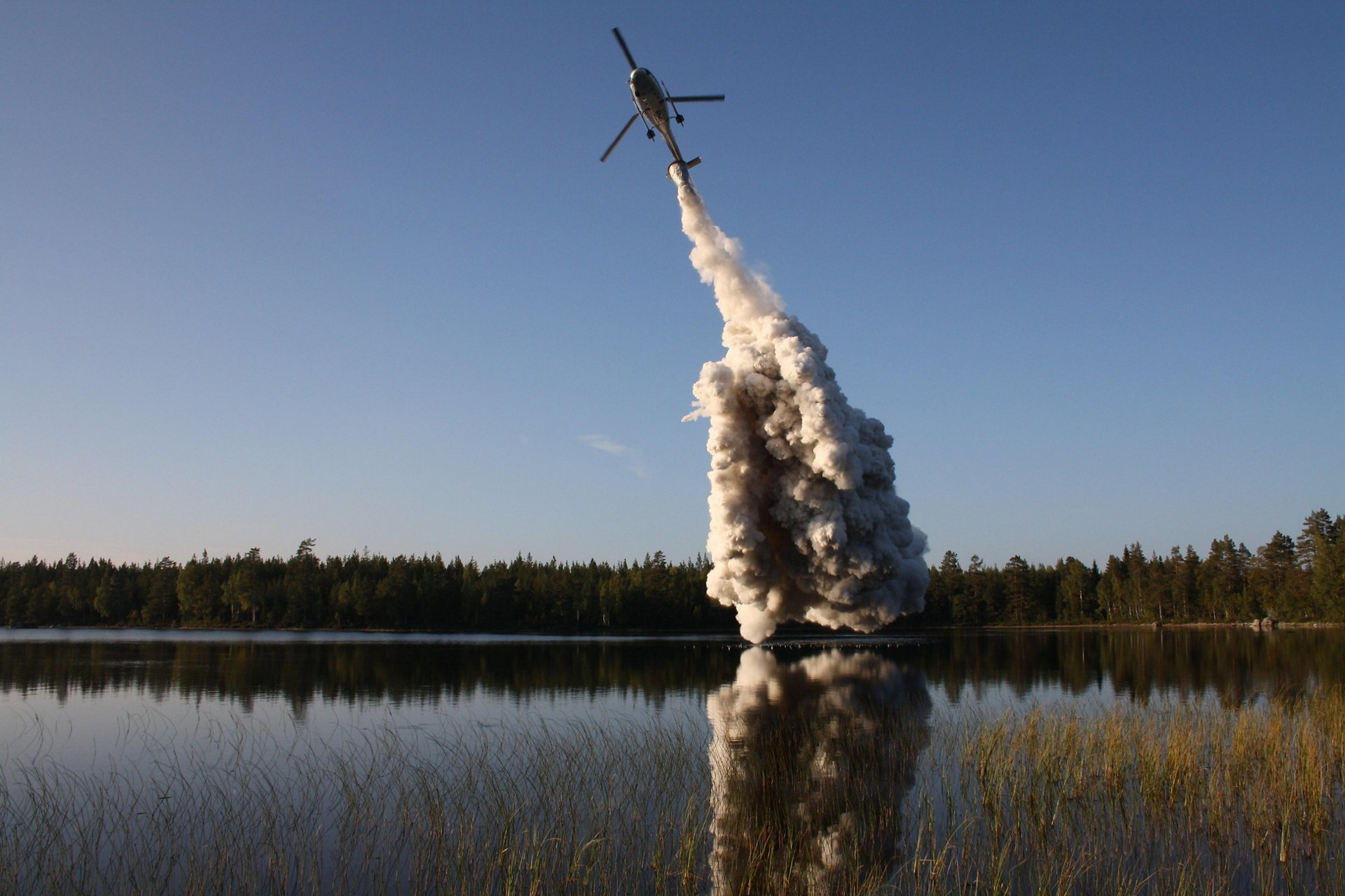 An H125 helicopter operated by Scandair sprays lime over a Scandinavian lake in order to lower freshwater pH levels.