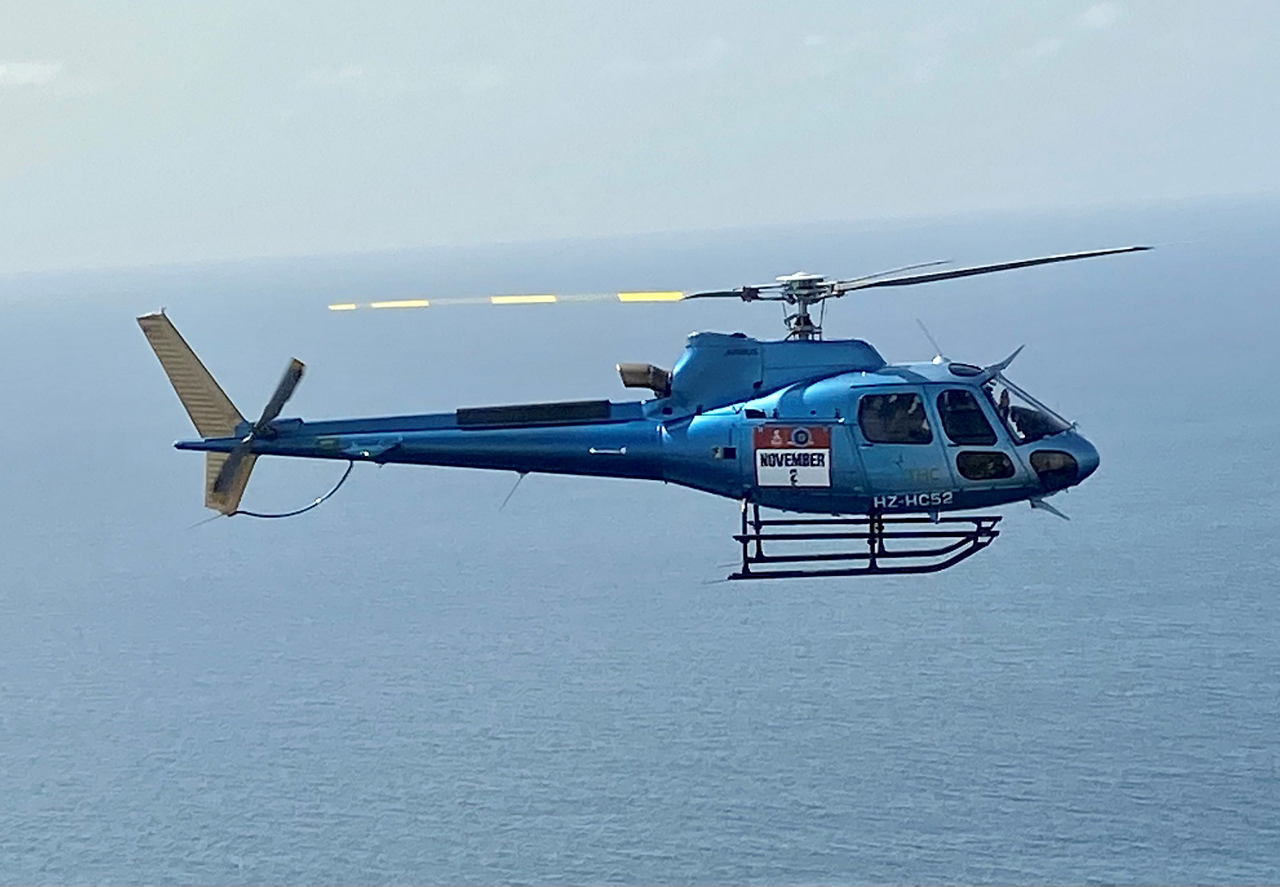 An H125 rotorcraft operated by The Helicopter Company (THC) is shown in flight at the 2021 Dakar Rally in Saudi Arabia.