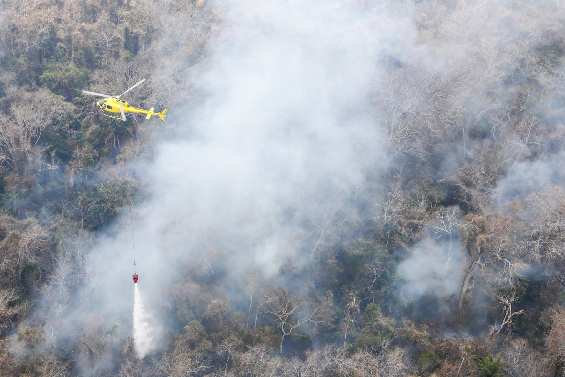An H125 helicopter supports firefighting efforts with deployment of a bucket-type water dispersal system.