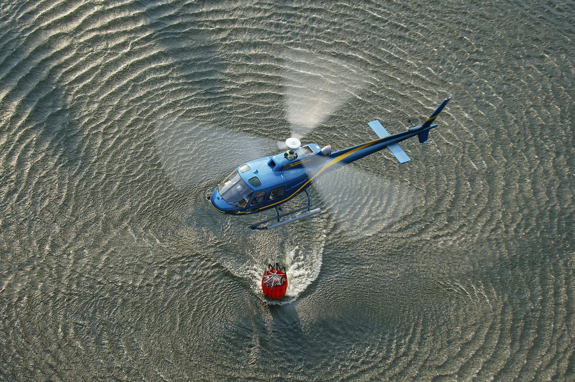 An Airbus-built helicopter loads its bucket-type water dispersal system in a dipping operation.