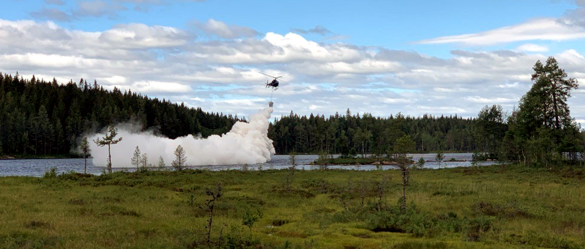 An H125 operated by Scandair of Sweden sprays lime over a Scandinavian lake in order to lower freshwater pH levels.