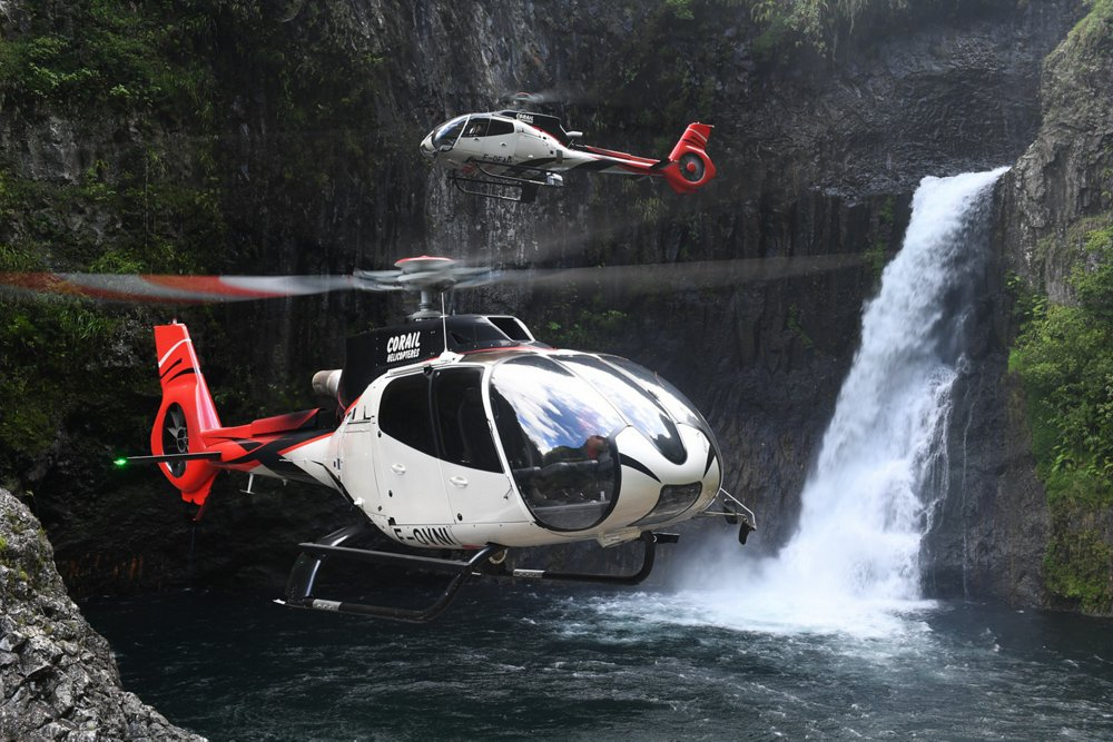 Two Airbus H130 helicopters perform sightseeing missions at a scenic location