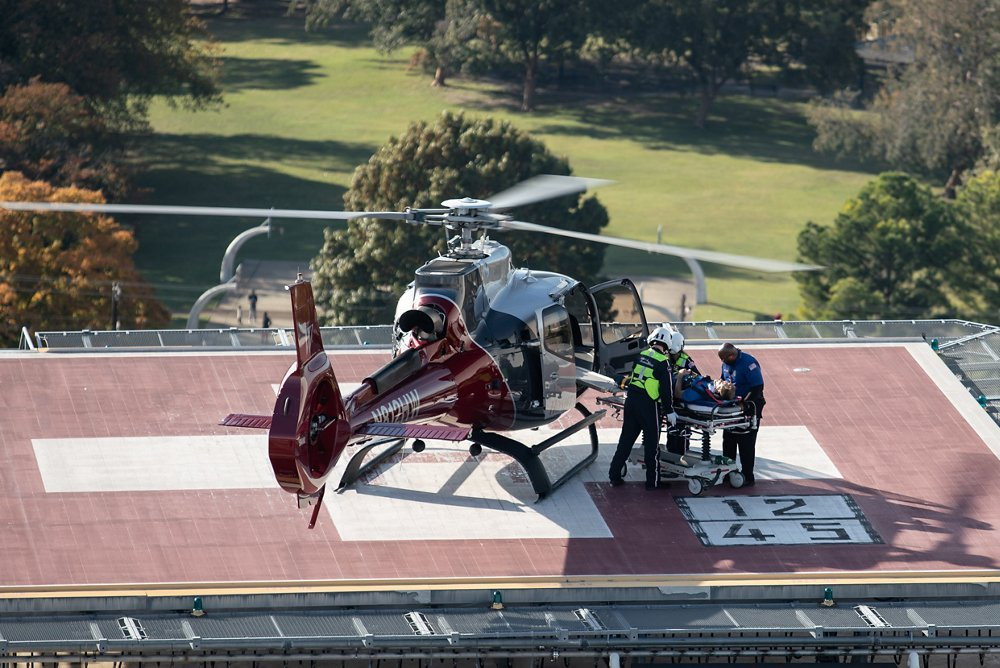 A patient is unloaded from an Airbus H130 helicopter outfitted for air ambulance operations