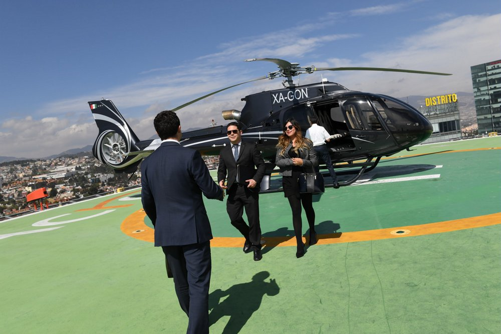 Two professionals walk away after disembarking from an Airbus H130 helicopter tailored for private/business aviation