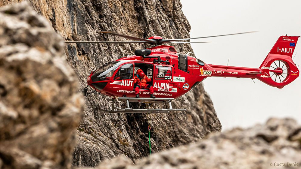 In-flight photo of an H135 helicopter operated by Aiut Alpin Dolomites.
